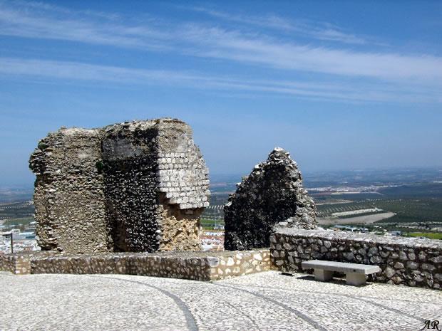 Castillo de Estepa. El recinto fortificado ocupa la parte alta del cerro en el que se ubica la villa. En la actualidad se conservan únicamente algunos lienzos y cubos de la muralla sobre todo en el sector sureste, alternando las de planta cuadrada con las semicirculares. En el lado oeste, próximo a la zona donde estaba la entrada principal del recinto y sirviendo de baluarte defensivo, se alza el antiguo alcázar o castillo, del cual se conserva la Torre del Homenaje. Ésta fue en origen una torre albarrana conectada con el alcázar propiamente dicho. Posee solamente una cámara en la parte alta cubierta con bóveda gótica de ocho nervios de piedra con plementería de ladrillo. Su planta es cuadrada, de 13 metros de lado a ras del suelo y de 12,5 metros en la parte superior. Su altura es de 26 metros. La construcción es de sillares a soga y tizón en el zócalo hasta la sexta hilada. También son de sillares las esquinas y el macizo en el que se abren las ventanas y la puerta de acceso, como también las ménsulas de los ángulos y el matacán sobre la puerta. El resto del paramento es de tapial. La parte maciza tiene 12,5 metros de altura, a cuyo nivel se halla una cámara de planta cuadrada de 7,35 metros de lado, cubierta con una bóveda de crucería octogonal. La entrada de la cámara está a levante en el mismo lienzo de pared de la entrada y en su ángulo con el muro sur se abre la puerta de acceso a la escalera de la azotea, cubierta por tres tramos de bóveda escalonados, la primera vaída, la segunda de artesa y la tercera de cañón apuntado. La terraza que corona la torre carece de parapeto hoy día.