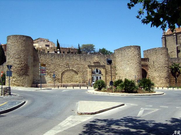 """Puerta de Almocábar y Murallas de Almocábar. La Puerta de Almocábar se encuentra situada en el sector sur de la medina, construida en el siglo XIII y reestructurada en el periodo de Carlos V. Esta puerta toma su nombre de la palabra """"Al-maqabir"""", cementerio, por estar cerca de la necrópolis principal extramuros, según costumbre islámica. Fue una de las puertas principales de acceso a la ciudad y daba entrada al Barrio Alto, actualmente del Espíritu Santo y a la medina musulmana."""
